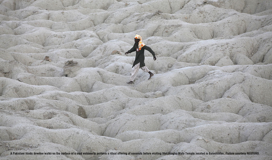 A Pakistani Hindu devotee walks on the surface of a mud volcano to perform a ritual offering of coconuts before visiting Shri Hinglaj Mata Temple located in Balochistan province