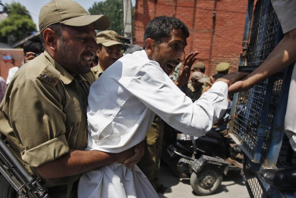 An Indian policeman detains a member of All Jammu and Kashmir Handicapped Association during protest in Srinagar