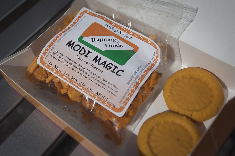 "A box containing a bag of snacks labelled ""Modi Magic"" is pictured while a large crowd of people in Times Square watch the speech by India's PM Modi simulcast on a giant screen in New York"