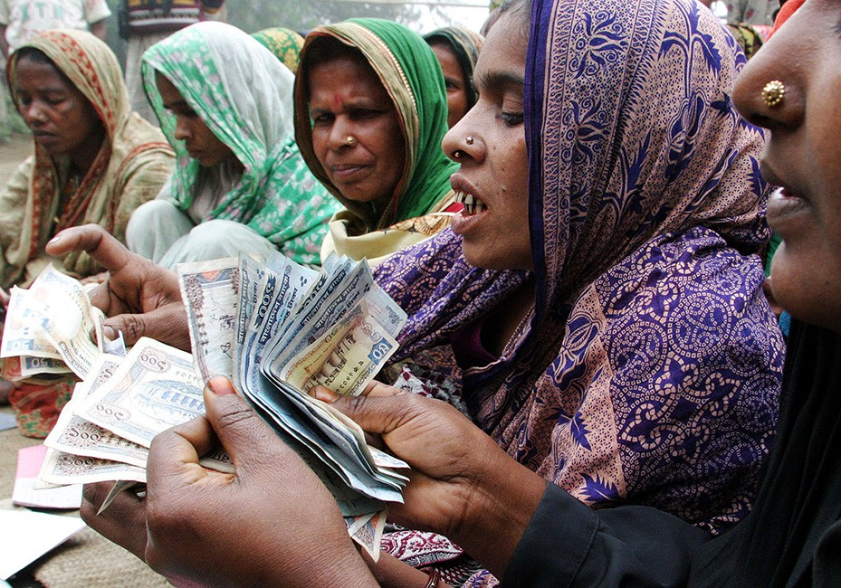 Bangladeshi women count money for repayment to a microcredit bank at Dowtia village, near Dhaka. Once living hand to mouth, now the women earn an adequate amount to support their families by running small projects of cattle breeding or poultry farming with loans from BRAC, the biggest of a legion of non-government organisations that has pioneered microfinance as a means of helping the poor to help themselves. Picture taken on January 20, 2004. REUTERS/Rafiqur Rahman  NA/SH - RTRBM7O